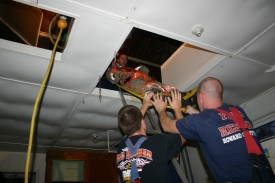 Kyle Goldman, Peter Nash, and Jonathon McKee assist in lowering a patient from the attic during Training/House Burn Nov 12, 2006 Transco Road