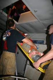 Justin Sosebee, Peter Nash, and Jonathon McKee assist in lowering a patient from the attic during Training/House Burn Nov 12, 2006 Transco Road