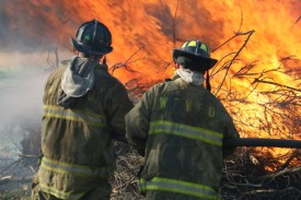 Justin Sosebee and Jimmy Garratt monitoring a pile of brush burning. - Transco Road